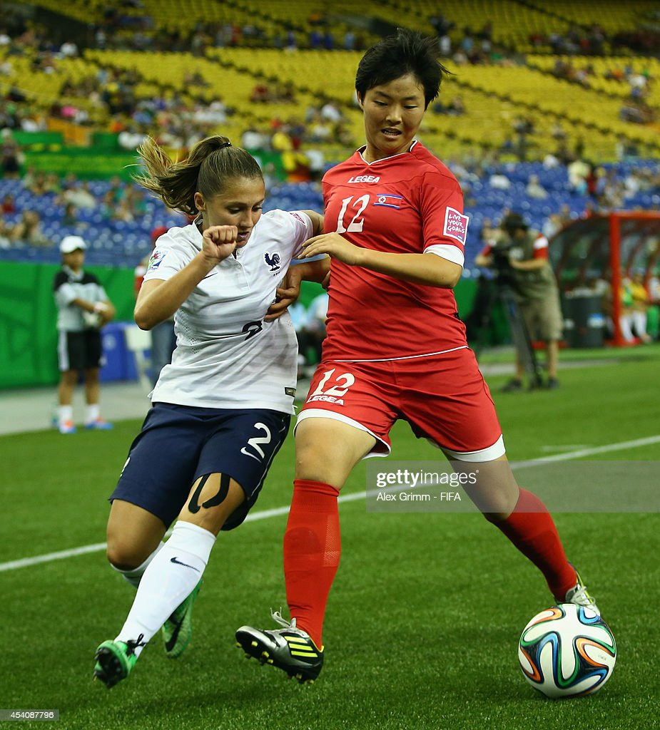 Jon So Yon (R) of Korea DPR is challenged by Eve Perisset of France during the FIFA U-20 Women's World Cup Canada 2014 3rd place match between Korea DPR and France at Olympic Stadium on August 24, 2014 in Montreal, Canada.