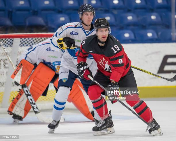Jonah Gadjovich of Canada battles for position with Urho Vaakanainen of Finland during a World Jr Summer Showcase game at USA Hockey Arena on August...