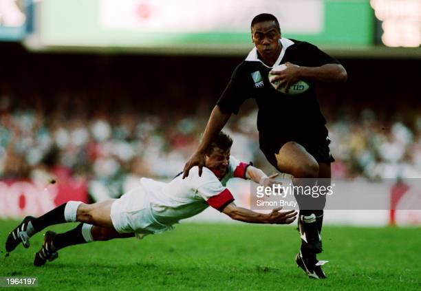 Jonah Lomu of New Zealand evades a challenge from Rob Andrew of England during the Rugby World Cup semi final between England and New Zealand on June...
