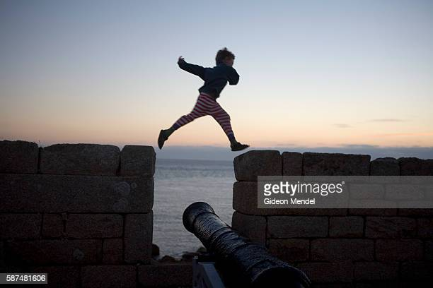 Jonah Mendel leaps over a gap in the Woolpack Point Battery on St Mary's island in the Scilly Isles This is a popular resting point on the short walk...