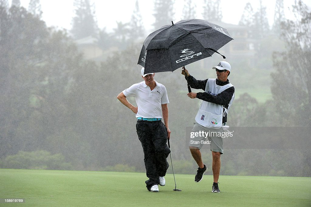 Jonas Blixt of Sweden (L) and caddie take cover from the rain on the ninth green waits to putt on the ninth hole during the Pro-Am round for the Hyundai Tournament of Champions at Plantation Course at Kapalua on January 3, 2013 in Kapalua, Hawaii.