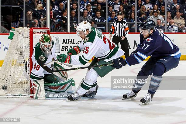 Jonas Brodin of the Minnesota Wild and Adam Lowry of the Winnipeg Jets chase the loose puck as goaltender Devan Dubnyk guards the net during second...