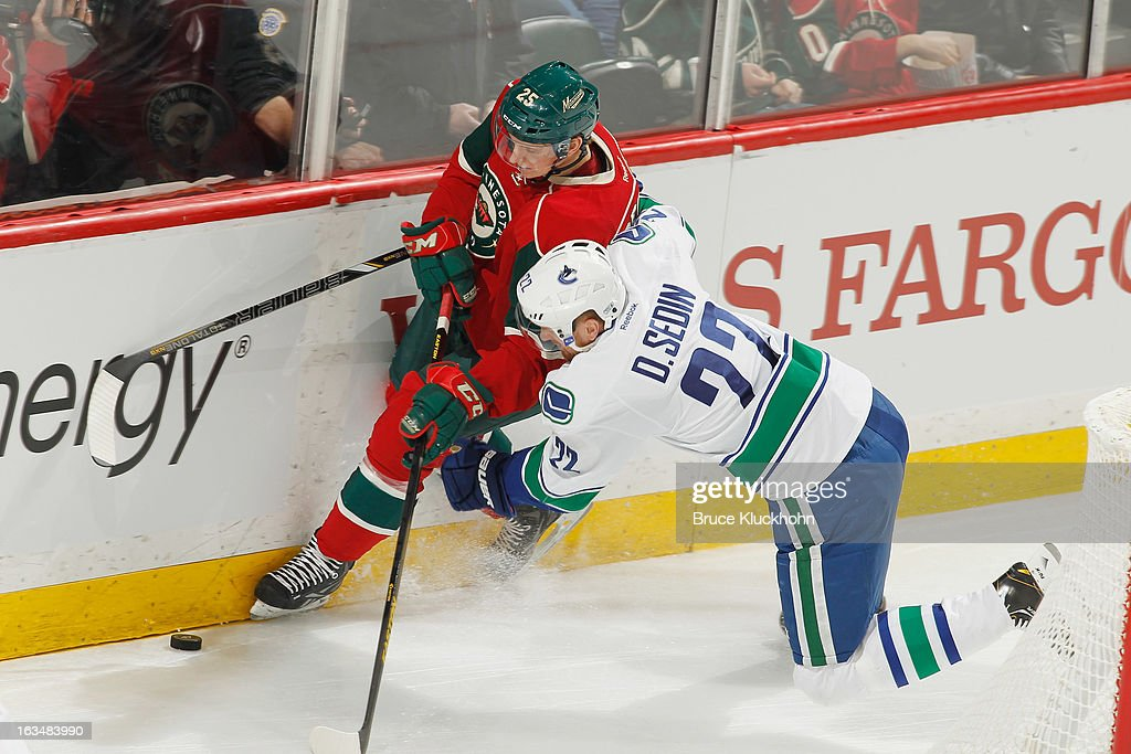 Jonas Brodin #25 of the Minnesota Wild and Daniel Sedin #22 of the Vancouver Canucks battle for the puck along the boards during the game on March 10, 2013 at the Xcel Energy Center in Saint Paul, Minnesota.