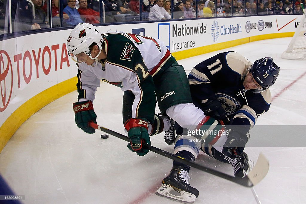 Jonas Brodin #25 of the Minnesota Wild and Matt Calvert #11 of the Columbus Blue Jackets battle for control of a loose puck during the second period on April 7, 2013 at Nationwide Arena in Columbus, Ohio.