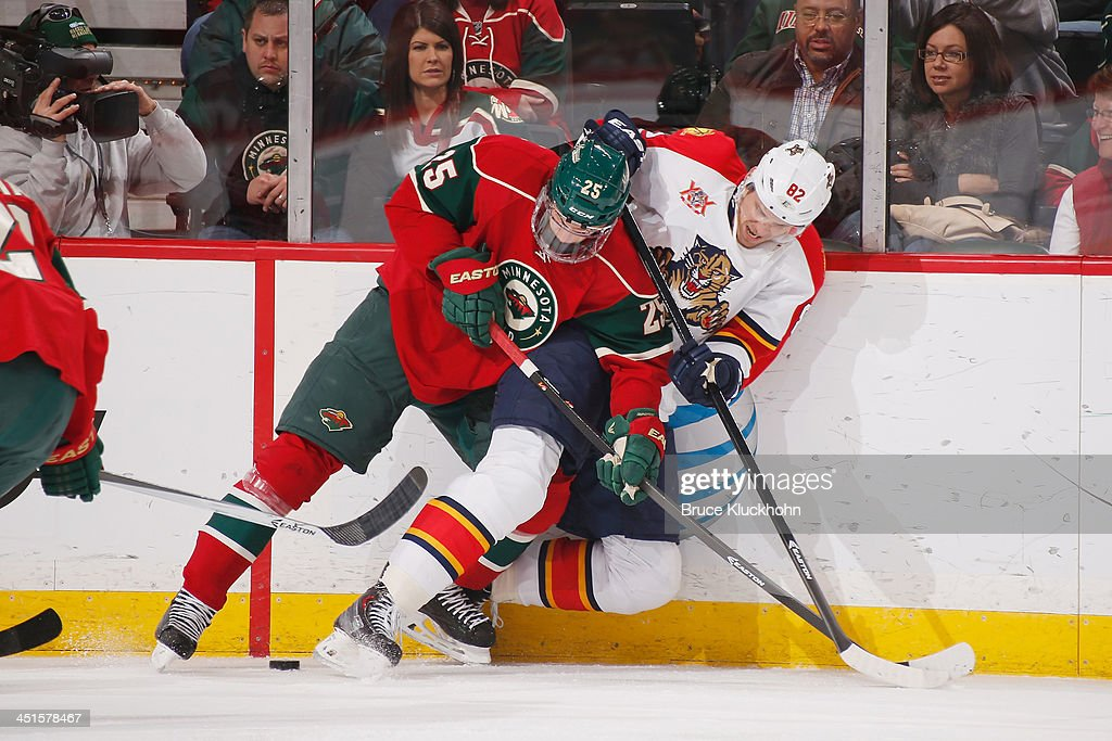 Jonas Brodin #25 of the Minnesota Wild and Tomas Kopecky #82 of the Florida Panthers battle for the puck along the boards during the game on November 15, 2013 at the Xcel Energy Center in St. Paul, Minnesota.