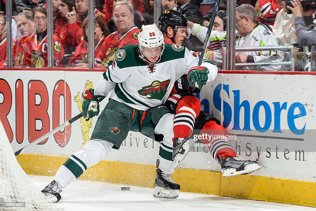 Jonas Brodin of the Minnesota Wild checks Jonathan Toews of the Chicago Blackhawks during the NHL game at the United Center on April 7 2015 in...
