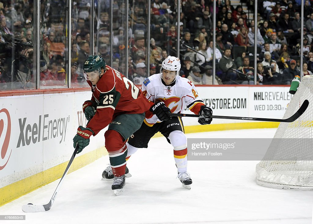 Jonas Brodin #25 of the Minnesota Wild controls the puck against Jiri Hudler #24 of the Calgary Flames during the first period of the game on March 3, 2014 at Xcel Energy Center in St Paul, Minnesota.