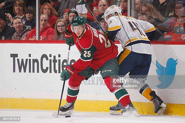 Jonas Brodin of the Minnesota Wild handles the puck with Taylor Beck of the Nashville Predators defending during the game on January 10 2015 at the...
