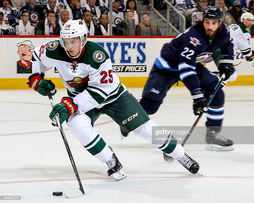 Jonas Brodin #25 of the Minnesota Wild plays the puck away from Chris Thorburn #22 of the Winnipeg Jets during second period action at the MTS Centre on October 25, 2015 in Winnipeg, Manitoba, Canada. The Jets defeated the Wild 5-4.