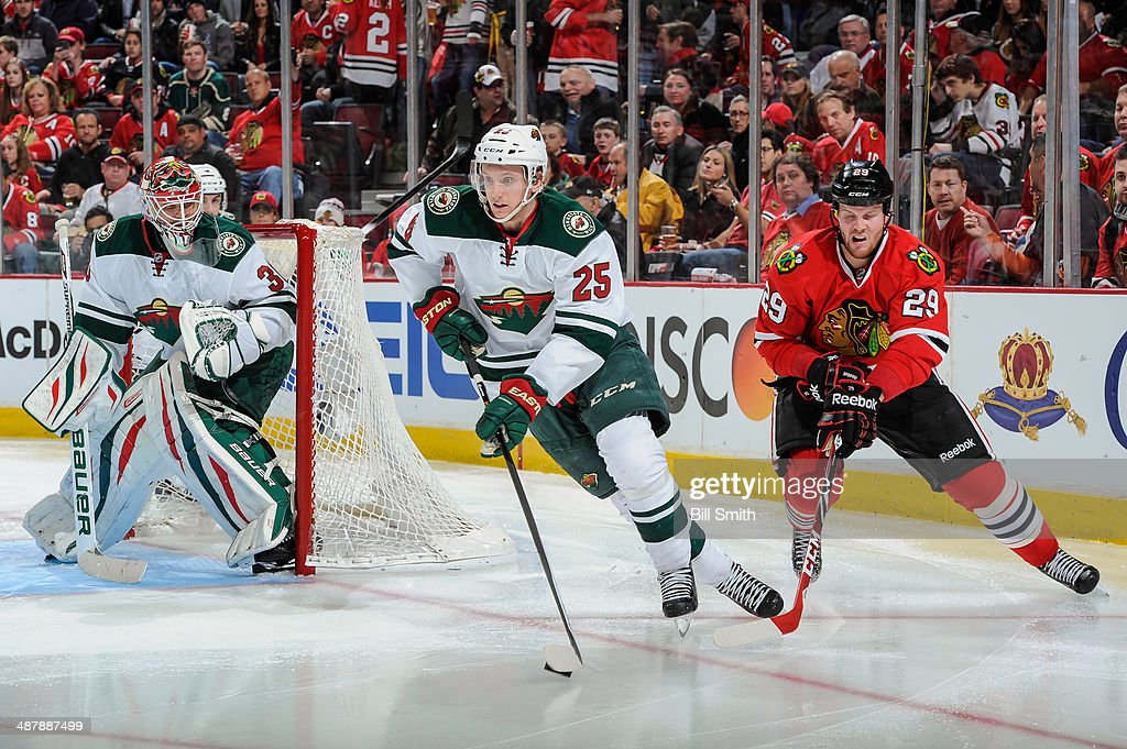 Jonas Brodin #25 of the Minnesota Wild takes control of the puck in front of Bryan Bickell #29 of the Chicago Blackhawks, as goalie Ilya Bryzgalov #30 of the Wild guards the net, in Game One of the Second Round of the 2014 Stanley Cup Playoffs at the United Center on May 02, 2014 in Chicago, Illinois.