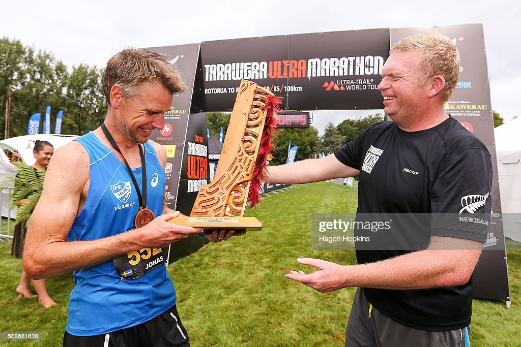 Jonas Buud of Sweden receives the winner's trophy from event organiser Paul Charteris during the Tarawera Ultramarathon on February 6, 2016 in Rotorua, New Zealand.