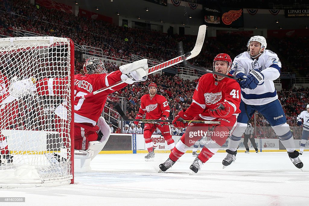 <a gi-track='captionPersonalityLinkClicked' href=/galleries/search?phrase=Jonas+Gustavsson&family=editorial&specificpeople=886789 ng-click='$event.stopPropagation()'>Jonas Gustavsson</a> #50 and <a gi-track='captionPersonalityLinkClicked' href=/galleries/search?phrase=Luke+Glendening&family=editorial&specificpeople=5650380 ng-click='$event.stopPropagation()'>Luke Glendening</a> #41 of the Detroit Red Wings battle for an airborne puck with <a gi-track='captionPersonalityLinkClicked' href=/galleries/search?phrase=Ryan+Callahan&family=editorial&specificpeople=809690 ng-click='$event.stopPropagation()'>Ryan Callahan</a> #24 of the Tampa Bay Lightning during an NHL game on March 30, 2014 at Joe Louis Arena in Detroit, Michigan.