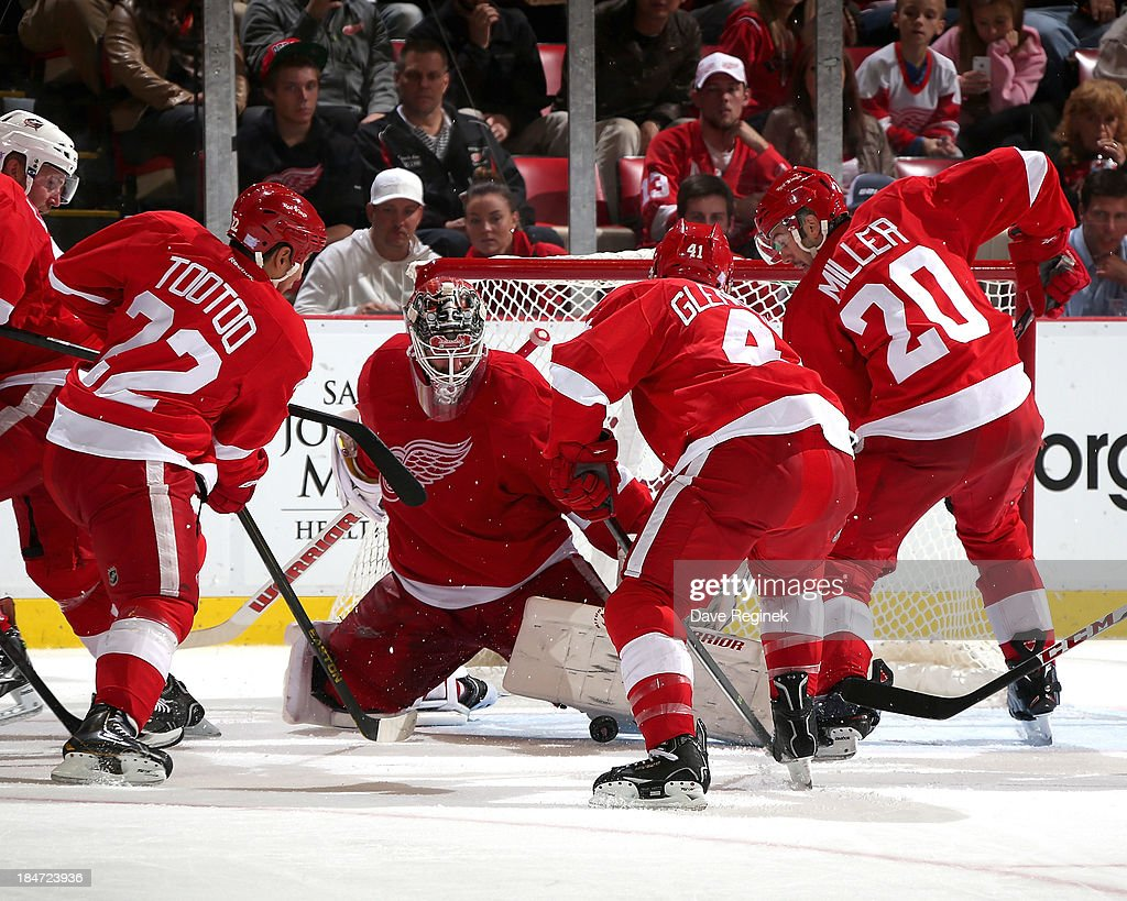 <a gi-track='captionPersonalityLinkClicked' href=/galleries/search?phrase=Jonas+Gustavsson&family=editorial&specificpeople=886789 ng-click='$event.stopPropagation()'>Jonas Gustavsson</a> #50 of the Detroit Red Wings makes a big pad save while his teammates <a gi-track='captionPersonalityLinkClicked' href=/galleries/search?phrase=Jordin+Tootoo&family=editorial&specificpeople=203013 ng-click='$event.stopPropagation()'>Jordin Tootoo</a> #22, Drew Miller #20 and Luke Glendening #41 protect the rebound in the front of the net during a NHL game against the Columbus Blue Jackets at Joe Louis Arena on October 15, 2013 in Detroit, Michigan. Detroit defeated Columbus 2-1