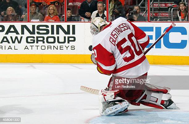 Jonas Gustavsson of the Detroit Red Wings makes a glove save against the Philadelphia Flyers on October 25 2014 at the Wells Fargo Center in...