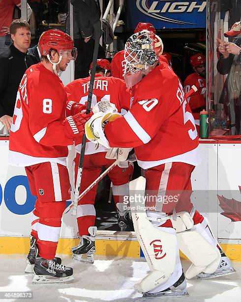 Jonas Gustavsson of the Detroit Red Wings taps gloves with Justin Abdelkader on the way to the locker room after an NHL game against the Montreal...