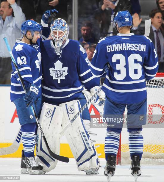 Jonas Gustavsson of the Toronto Maple Leafs is congratualted upon winning by teammates Nazem Kadri and Carl Gunnasson after a game against the...