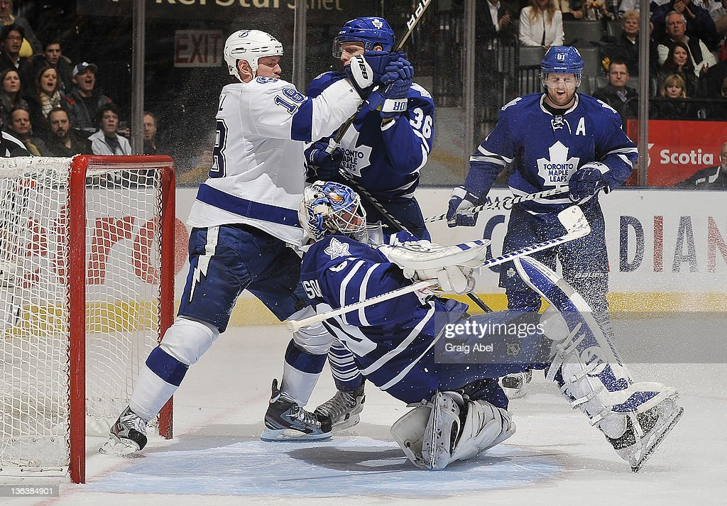 Jonas Gustavsson of the Toronto Maple Leafs is knocked over as teammate Carl Gunnarsson battles with Adam Hall of the Tampa Bay Lightning during NHL...