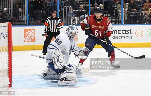 Jonas Gustavsson of the Toronto Maple Leafs makes a save in front of Maxim Afinogenov of the Atlanta Thrashers at Philips Arena on March 25 2010 in...