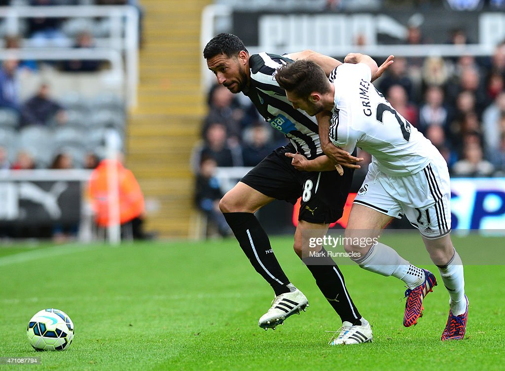 Jonas Gutierrez of Newcastle is tackled by Matt Grimes of Swansea City during the Barclays Premier League match between Newcastle United and Swansea City at St James' Park on April 25, 2015 in Newcastle upon Tyne, England.