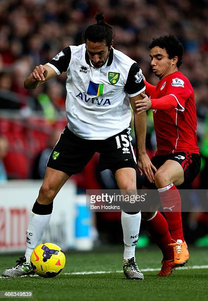 Jonas Gutierrez of Norwich holds off pressure from Fabio da Silva of Cardiff during the Barclays Premier League match between Cardiff City and...