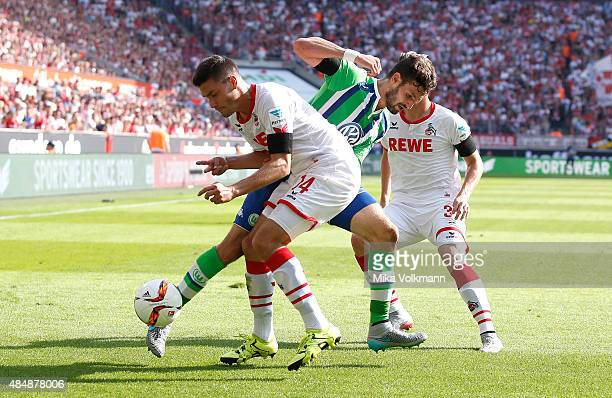 Jonas Hector of Cologne L9 challenges Daniel Caligiuri of Wolfsburg during the Bundesliga match between 1 FC Koeln and VfL Wolfsburg at...