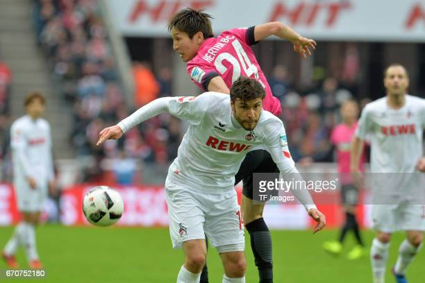 Jonas Hector of Colonge and Genki Haraguchi of Berlin battle for the ball during the Bundesliga match between 1 FC Koeln and Hertha BSC at...