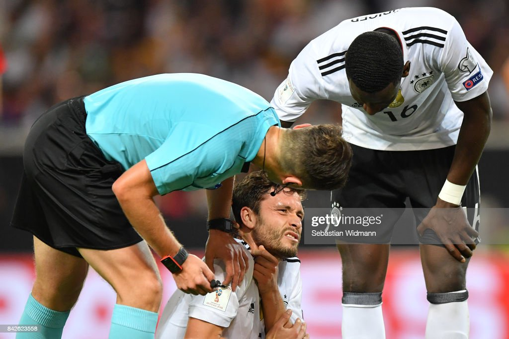 Jonas Hector of Germany is being checked on by referee Gediminas Mazeika (l) and Antonio Ruediger of Germany during the FIFA 2018 World Cup Qualifier between Germany and Norway at Mercedes-Benz Arena on September 4, 2017 in Stuttgart, Baden-Wuerttemberg.