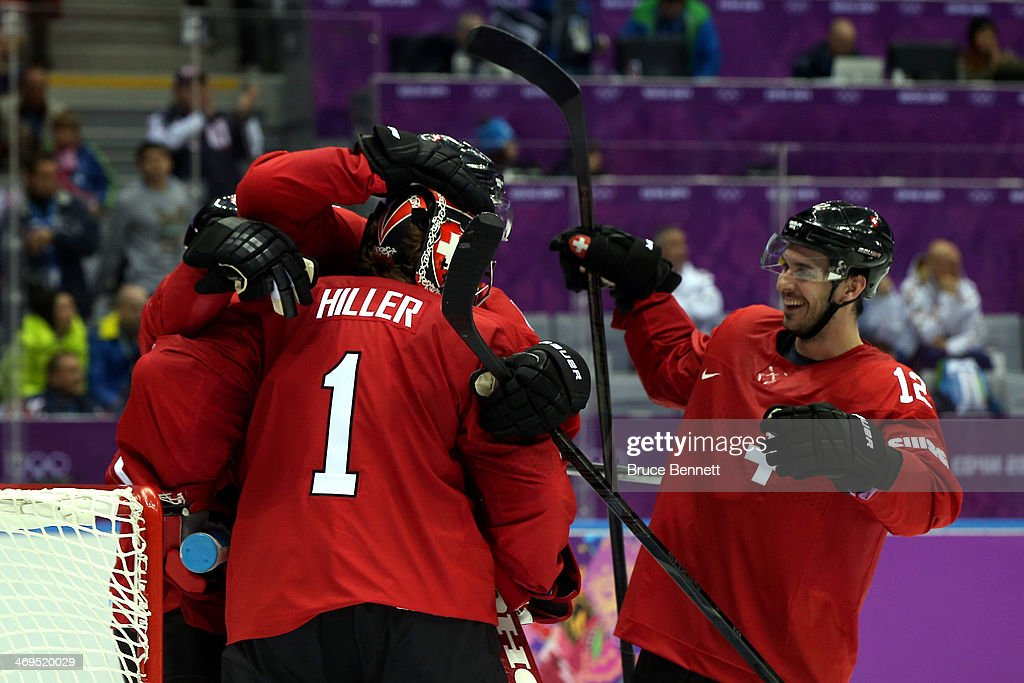 Jonas Hiller #1 of Switzerland celebratse with his teammate Luca Cunti #12 after defeating the Czech Republic 1 to 0 in the Men's Ice Hockey Preliminary Round Group C game on day eight of the Sochi 2014 Winter Olympics at Bolshoy Ice Dome on February 15, 2014 in Sochi, Russia.