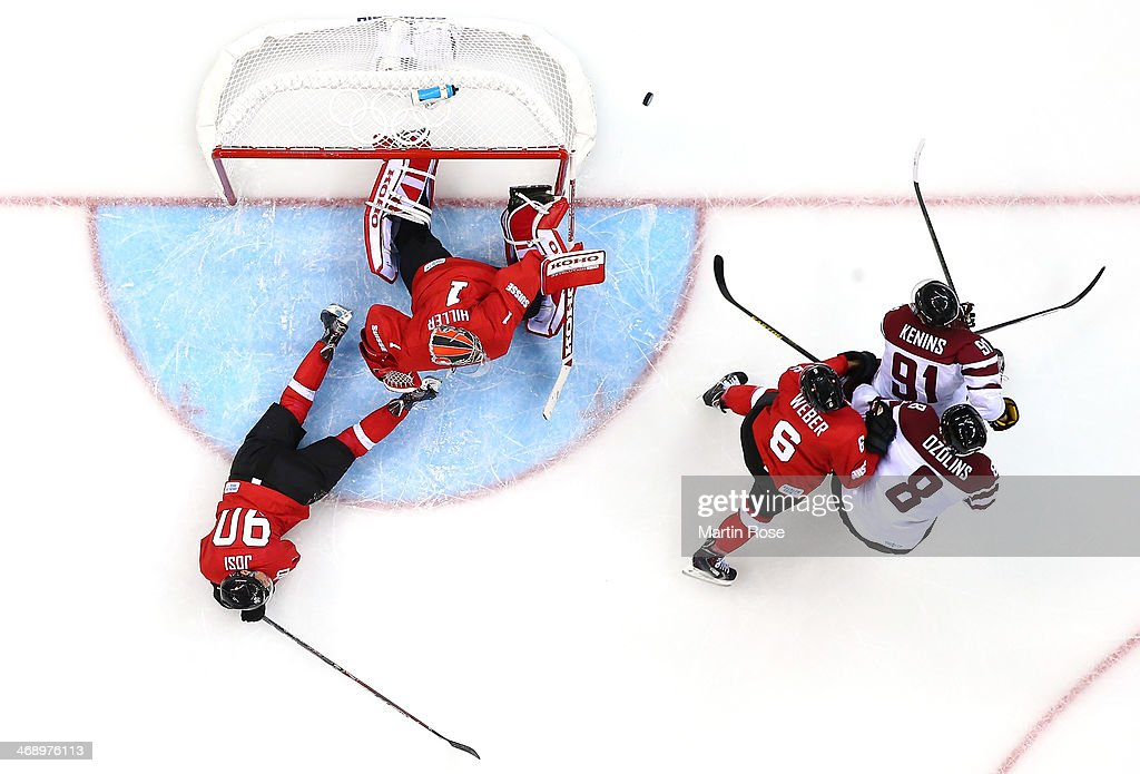 <a gi-track='captionPersonalityLinkClicked' href=/galleries/search?phrase=Jonas+Hiller&family=editorial&specificpeople=743364 ng-click='$event.stopPropagation()'>Jonas Hiller</a> #1 of Switzerland makes a save against Sandis Ozolins #8 and Ronalds Kenins #91 of Latvia as <a gi-track='captionPersonalityLinkClicked' href=/galleries/search?phrase=Roman+Josi&family=editorial&specificpeople=4247871 ng-click='$event.stopPropagation()'>Roman Josi</a> #90 and <a gi-track='captionPersonalityLinkClicked' href=/galleries/search?phrase=Yannick+Weber&family=editorial&specificpeople=4324944 ng-click='$event.stopPropagation()'>Yannick Weber</a> #6 defend in the third period during the Men's Ice Hockey Preliminary Round Group C game on day five of the Sochi 2014 Winter Olympics at Shayba Arena on February 12, 2014 in Sochi, Russia.