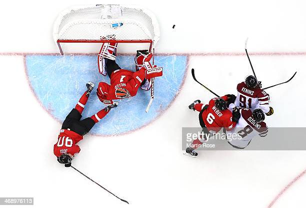 Jonas Hiller of Switzerland makes a save against Sandis Ozolins and Ronalds Kenins of Latvia as Roman Josi and Yannick Weber defend in the third...