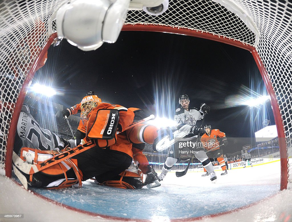 <a gi-track='captionPersonalityLinkClicked' href=/galleries/search?phrase=Jonas+Hiller&family=editorial&specificpeople=743364 ng-click='$event.stopPropagation()'>Jonas Hiller</a> #1 of the Anaheim Ducks makes a save as <a gi-track='captionPersonalityLinkClicked' href=/galleries/search?phrase=Jeff+Carter&family=editorial&specificpeople=227320 ng-click='$event.stopPropagation()'>Jeff Carter</a> #77 of the Los Angeles Kings looks for a rebound during the 2014 Coors Light NHL Stadium Series at Dodger Stadium on January 25, 2014 in Los Angeles, California. The Ducks won 3-0.