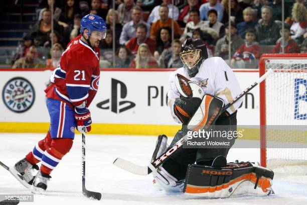 Jonas Hiller of the Anaheim Ducks stops the puck in front of Brian Gionta of the Montreal Canadiens during the NHL game at the Bell Centre on January...
