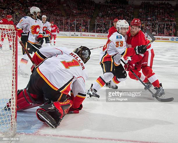 Jonas Hiller of the Calgary Flames covers the puck as teammate Raphael Diaz defends Joakim Andersson of the Detroit Red Wings during a NHL game on...