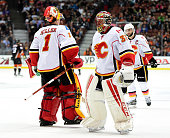Jonas Hiller of the Calgary Flames leaves the game as he is replaced by Niklas Backstrom of the Calgary Flames after allowing three goals to the...