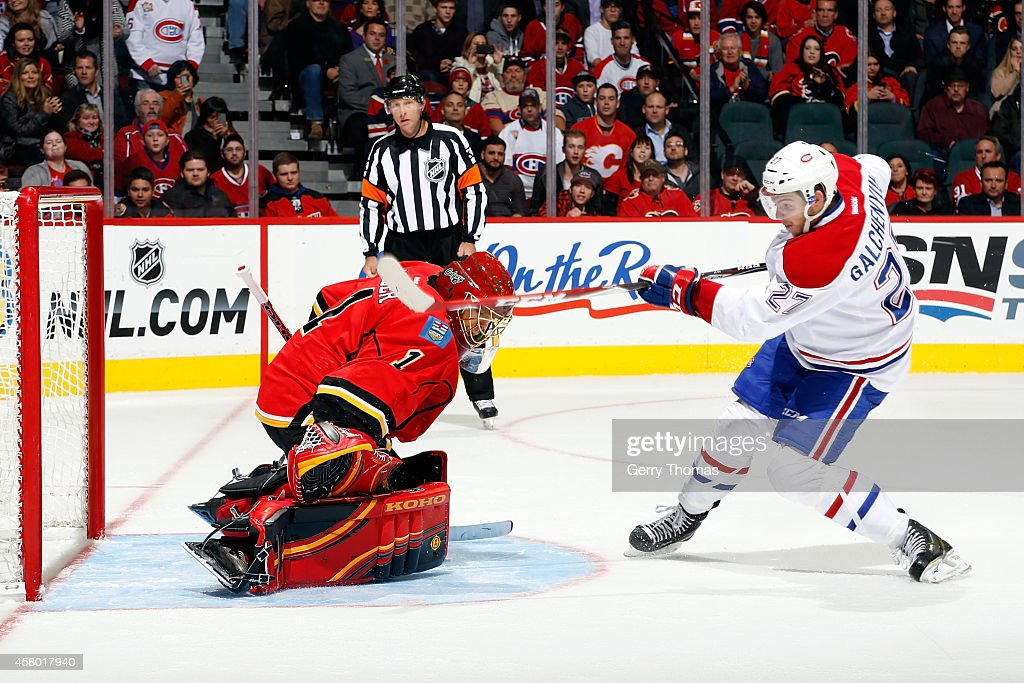 Jonas Hiller #1 of the Calgary Flames makes a save against Alex Galchenyuk #27 of the Montreal Canadiens at Scotiabank Saddledome on October 28, 2014 in Calgary, Alberta, Canada.