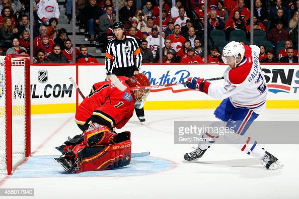 Jonas Hiller of the Calgary Flames makes a save against Alex Galchenyuk of the Montreal Canadiens at Scotiabank Saddledome on October 28 2014 in...