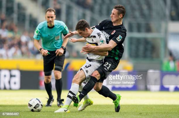 Jonas Hofmann of Borussia Moenchengladbach and Dominik Kohr of FC Augsburg battle for the ball during the Bundesliga Match between Borussia...