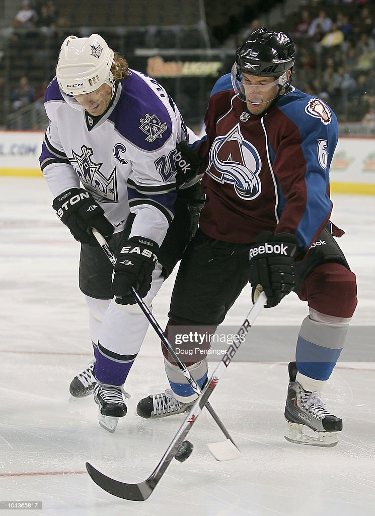 Jonas Holos #6 of the Colorado Avalanche and Michal Handzus #26 of the Los Angeles Kings battle for control of the puck during preseason NHL action at the Pepsi Center on September 22, 2010 in Denver, Colorado.