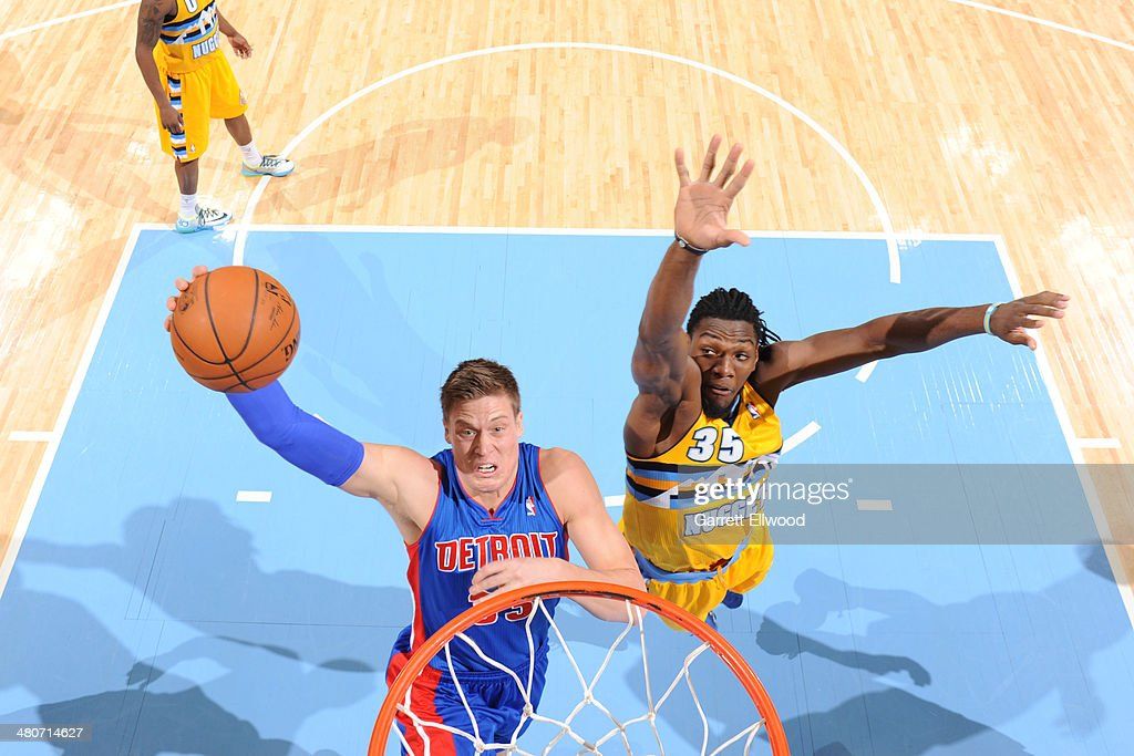 Jonas Jerebko #33 of the Detroit Pistons dunks against Kenneth Faried #35 of the Denver Nuggets on March 19, 2014 at the Pepsi Center in Denver, Colorado.