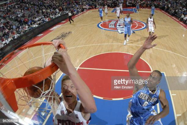 Jonas Jerebko of the Detroit Pistons dunks past Arron Afflalo of the Denver Nuggets in a game at the Palace of Auburn Hills on December 10 2009 in...