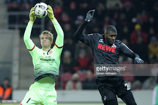 Jonas Loessl of Mainz makes a save against Anthony Modeste of Koeln during the Bundesliga match between 1 FSV Mainz 05 and 1 FC Koeln at Opel Arena...