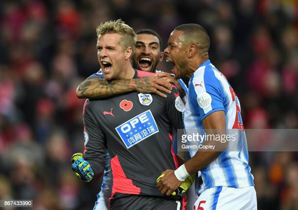 Jonas Lossl of Huddersfield Town celebrates saving a penalty with Danny Williams of Huddersfield Town and Mathias Jorgensen of Huddersfield Town...