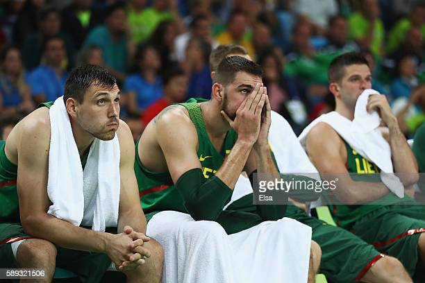 Jonas Maciulis Jonas Valanciunas and Mantas Kalnietis of Lithuania react on the bench during the Men's Preliminary Round Group B between Spain and...