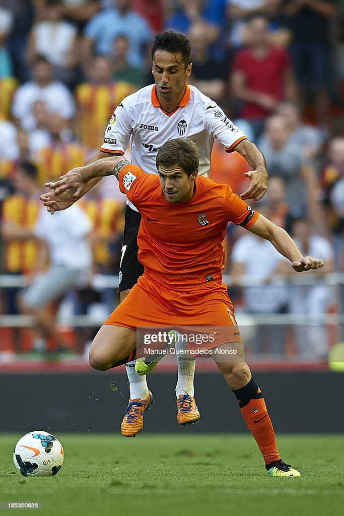 Jonas of Valencia competes for the ball with Inigo Martinez of Real Sociedad during the La Liga match between Valencia CF and Real Sociedad at...