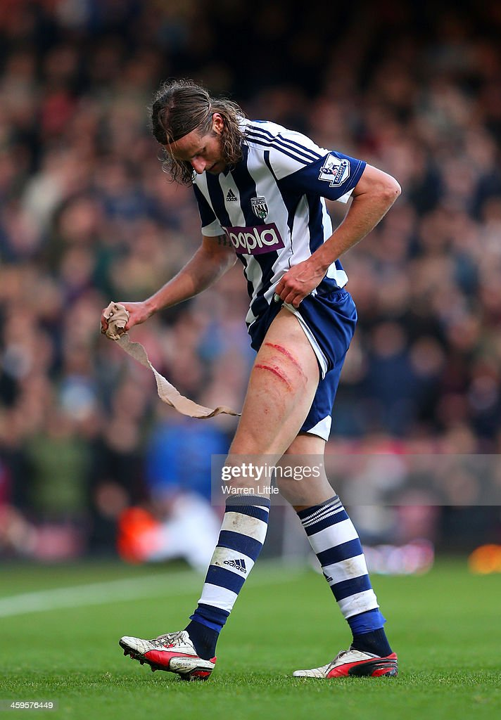 Jonas Olsson of West Brom removes a bandage from his leg during the Barclays Premier League match between West Ham United and West Bromwich Albion at Boleyn Ground on December 28, 2013 in London, England.