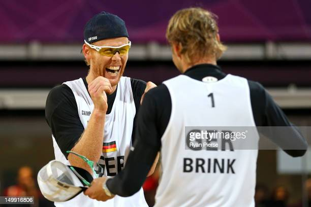 Jonas Reckermann and Julius Brink of Germany celebrate after they won match point against Ricardo Santos and Pedro Cunha of Brazil during the Men's...