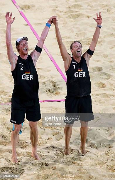 Jonas Reckermann and Julius Brink of Germany celebrate after they won match point against Alison Cerutti and Emanuel Rego of Brazil during the Men's...