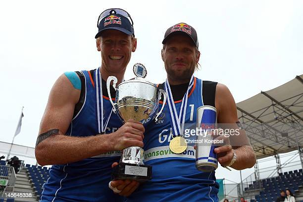 Jonas Reckermann and Julius Brink of Germany pose with the winning trophy after the men's final match between Emiel Boersma and Daan Spijkers of...