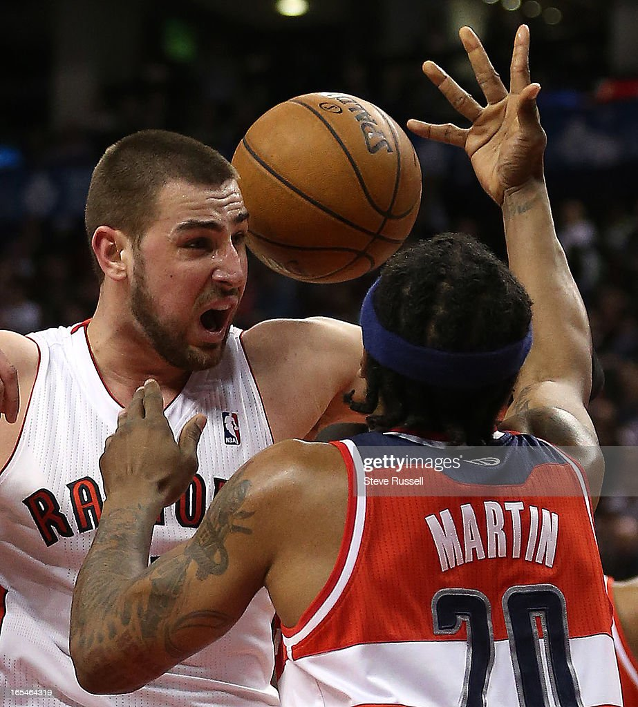 Jonas Valanciunas and Washington Wizards power forward Cartier Martin battle for a loose ball in second half action as the Toronto Raptors beat the Washington Wizards 88-78 at the Air Canada Centre in Toronto.