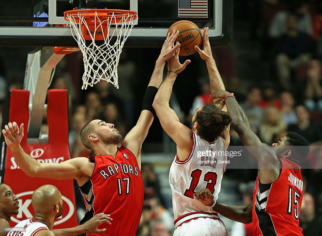 Jonas Valanciunas #17 of the Toronto Raptors blocks a shot by Joakim Noah #13 of the Chicago Bulls as Amir Johnson #15 defends at the United Center on December 14, 2013 in Chicago, Illinois.